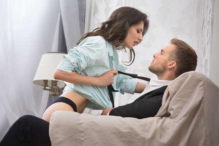 young couple sex: Сексуальная брюнетка соблазнила парня в деловом костюме, потянув его за галстук поцеловать. Пара сидит в большом кресле. Снято в студии интерьера.