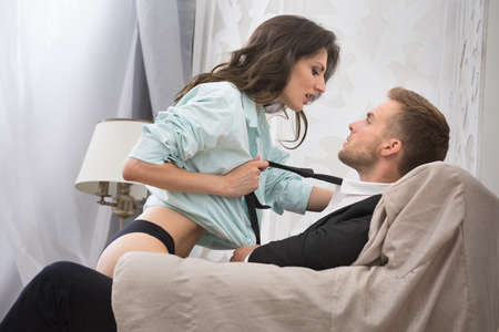 adult sex: Sexy brunette seduced a guy in a business suit pulling him by the tie to kiss. Couple sitting in a large armchair. Photographed in a studio interior. Stock Photo