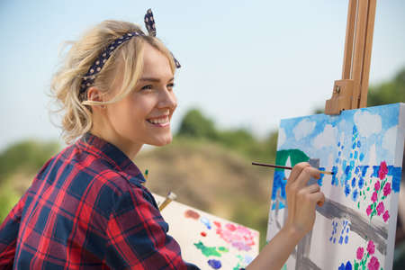 Beautiful blonde woman artist in a playful mood dressed in a plaid shirt. She paints a picture with a brush and paints nature Stockfoto