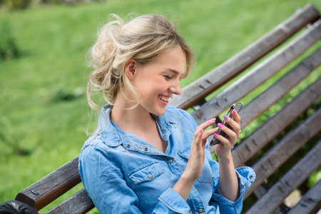 Cute blonde in a bright blue denim shirt emotionally talking on a cell phone. Stock Photo