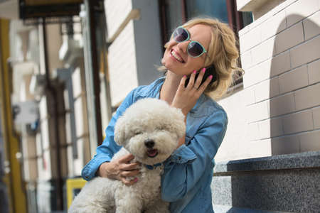 bichon: Cute blonde in sunglasses and a bright blue denim shirt emotionally talking on a cell phone. Bichon Frise white dog sitting on the lap of the girl.
