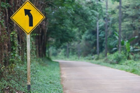 one lane street sign: Left Curve Ahead on the island road of Thailand Stock Photo