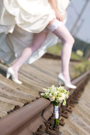 perspectiva lineal: ramo de la boda con las piernas de la novia en el riel de tren