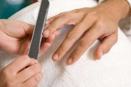 a man is getting manicure in salon