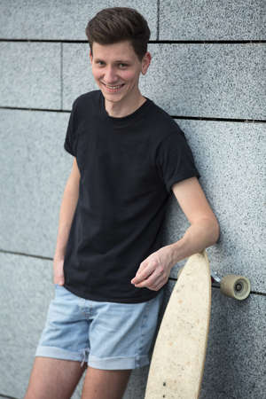 relying: Young boy stands near a wall lined with marble tiles relying on the longboard, with a smile, in a black T-shirt.