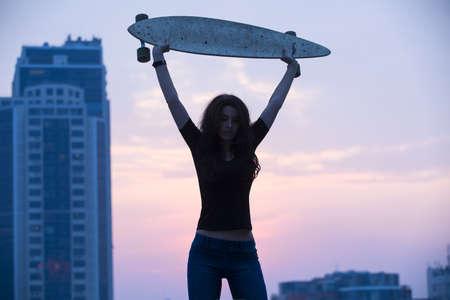 aloft: Stylish girl in jeans holding aloft longboard on a background of city sunset.
