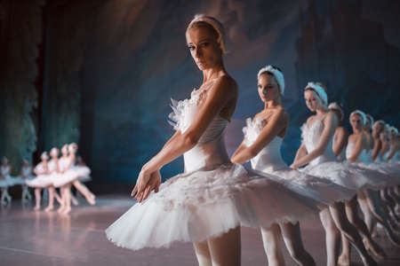 Dancers in white tutu synchronized dancing on stage. Repetition, editorial shooting.