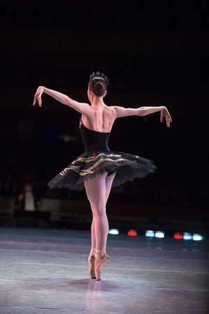 Prima ballerina dansen op een repetitie op het podium in een uitvoering van Swan Lake, van achteren gezien.