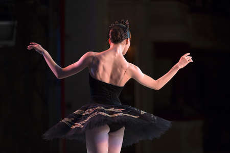 behind scenes: Prima ballerina dancing at a rehearsal on the stage in a performance of Swan Lake, seen from behind.