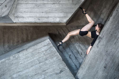 pointes: Flexible dancer posing lies between the complex geometry of concrete walls. Dancer lying on his back resting his toes in the opposite wall. The girl in black shorts and top pointes.