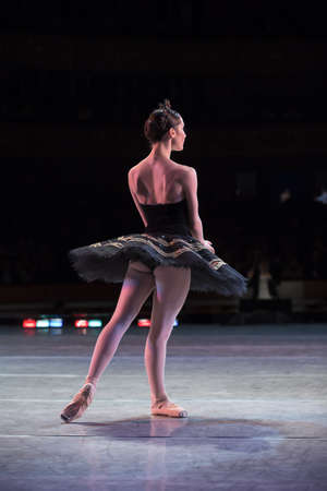 Prima ballerina dancing at a rehearsal on the stage in a performance of Swan Lake, seen from behind.