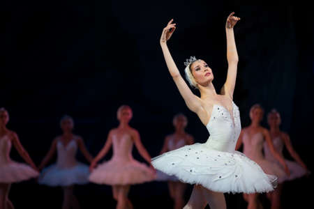 Prima ballerina white swan on stage dancing gracefully against other dancers. Ballet Swan Lake, the Opera House in Kiev, Ukraine. Standard-Bild