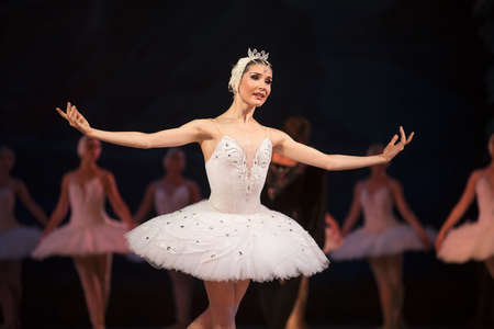 Prima ballerina white swan on stage dancing gracefully against other dancers. Ballet Swan Lake, the Opera House in Kiev, Ukraine. Zdjęcie Seryjne - 45500414