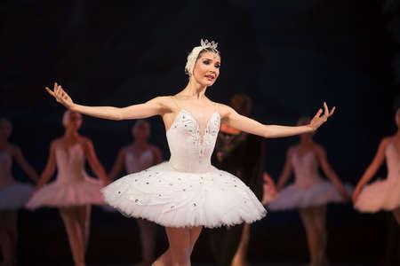 Prima ballerina white swan on stage dancing gracefully against other dancers. Ballet Swan Lake, the Opera House in Kiev, Ukraine. Zdjęcie Seryjne