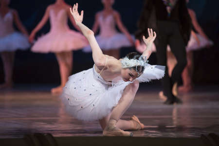 Prima ballerina white swan on stage bow and curtsey to the audience against other dancers. Ballet Swan Lake, the Opera House in Kiev, Ukraine.