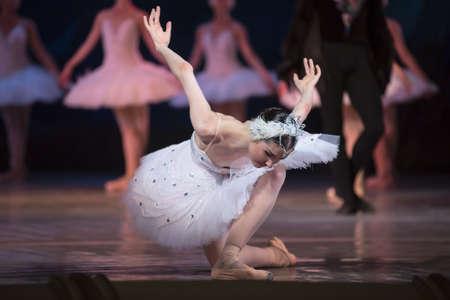 Primaballerina weißer Schwan auf der Bühne und Bogen Knicks an das Publikum gegen andere Tänzer. Ballett Schwanensee, das Opernhaus in Kiew, Ukraine. Standard-Bild - 45500424