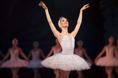 Prima ballerina white swan on stage dancing gracefully against other dancers. Ballet Swan Lake, the Opera House in Kiev, Ukraine. Zdjęcie Seryjne