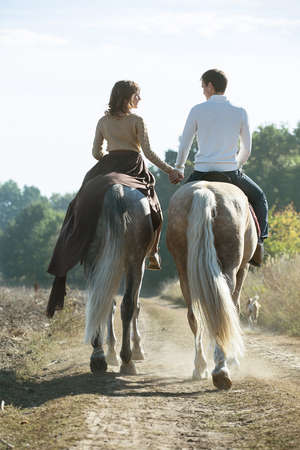 Young couple in love riding a horse walking on the background of autumn nature in a beautiful field. Couple pretty hold each other's hand. Zdjęcie Seryjne