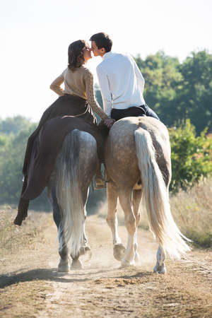 Young couple in love riding a horse walking on the background of autumn nature in a beautiful field. Couple pretty hold each others hand.