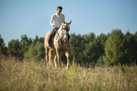 Attractive man on horseback, looking into the distance with a relaxed smile. Zdjęcie Seryjne