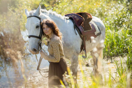 cowgirl and cowboy: Beautiful brunette in a lush skirt stands near a lake with a horse. She gently hugs and pats the horse. Stock Photo