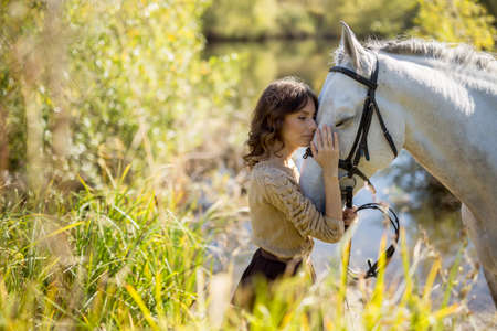 Beautiful brunette in a lush skirt stands near a lake with a horse. She gently hugs and pats the horse. Zdjęcie Seryjne