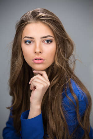 unruly: Portrait of a beautiful brown-haired girl with a deep look into the studio his chin in his hand. Model wearing a blue jacket. Thick unruly locks of hair develop from a light wind.