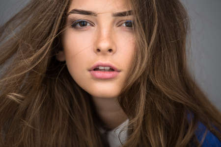 Close-up portrait of a beautiful brown-haired girl with a deep look into the studio. Model wearing a blue jacket. Thick unruly locks of hair develop from a light wind. Standard-Bild