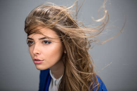 Portrait of a beautiful brown-haired girl with a deep look into the studio. Model wearing a blue jacket. Thick unruly locks of hair develop from a light wind.
