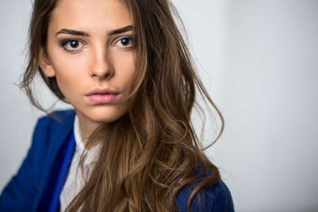 Close-up portrait of a beautiful brown-haired girl with a deep look into the studio. Model wearing a blue jacket. Thick unruly locks of hair develop from a light wind. Stock Photo