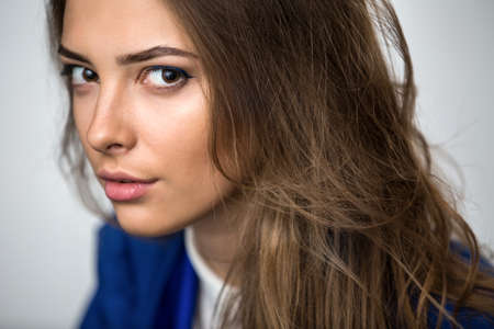 unruly: Close-up portrait of a beautiful brown-haired girl with a deep look into the studio. Model wearing a blue jacket. Thick unruly locks of hair develop from a light wind. Stock Photo
