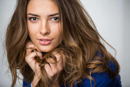 brown hair blue eyes: Close-up portrait of a beautiful brown-haired girl with a deep look into the studio. Model wearing a blue jacket. Thick unruly locks of hair develop from a light wind. Stock Photo