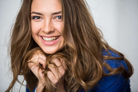 unruly: Close-up portrait of a beautiful brown-haired girl with smile with a deep look into the studio. Model wearing a blue jacket. Thick unruly locks of hair develop from a light wind. Stock Photo