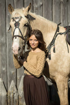 reins: Young attractive girl is walking with his horse, holding the reins.