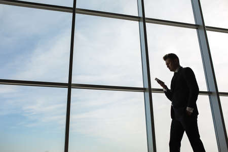 phone business: Stylish business man in the background of a large window in the floor. The model uses a mobile phone. Stock Photo