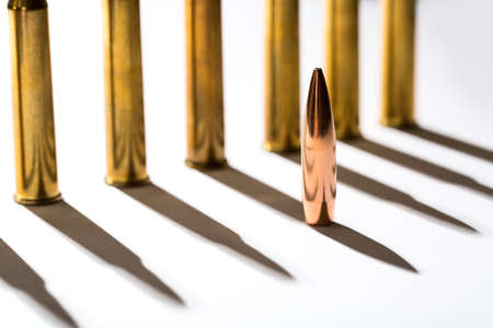 casings: Macro shot of bullet casings on a white studio background. Sleeve casts a shadow on the tough end of which is shiny copper bullet.