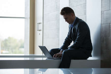transfers: Business man sitting alone on a bench with a laptop inside a building with a modern interior and large windows. Stock Photo