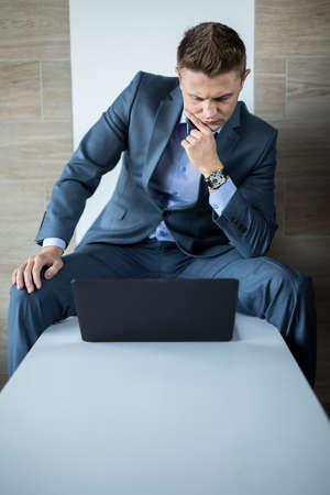 business skeptical: Retrato de un hombre guapo en una oficina de negocios de traje gris oscuro, simplemente. Un hombre se sienta en un banco de blanco y se queda mirando fijamente a la pantalla de su ordenador port�til, los apoyos mano podorodok esc�ptico.