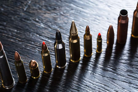 caliber: Number of large-caliber ammunition of different caliber in one line on a dark textural wooden background. Studio shot.
