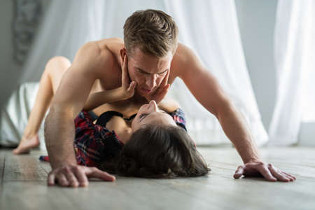 half nude: Young couple kissing lovers lounging on the floor. A guy with a naked torso is deposed girl and kisses her on the lips. The girl tenderly embraces his face in his hands both hands. Stock Photo
