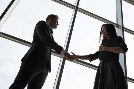 Business men and women shaking hands with a smile on the background of the large panoramic windows in a modern business center. Models dressed in a dark business suits. Zdjęcie Seryjne - 48554626