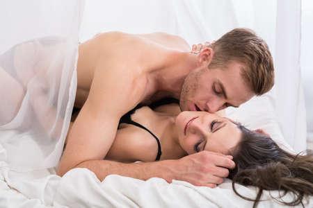 sexo pareja joven: Los j�venes enamorados se encuentran en la cama. Ma�ana rom�ntica con pasi�n. Foto de archivo
