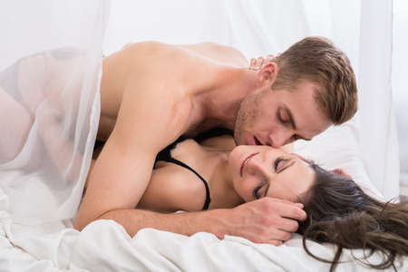man and woman sex: Young lovers lie in the bed. Romantic morning with passion.