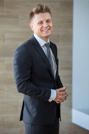 traje formal: Un hombre con un traje oscuro de pie con los brazos cruzados y sonriente.