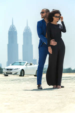 Business couple arrived in a white car to walk on a deserted beach in Dubai on the background of skyscrapers. The dark-haired girl in a black dress takes off his glasses. The dark-haired man with a beard wearing a blue suit embracing his girlfriend and gl Zdjęcie Seryjne