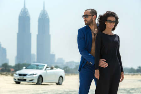 Fashionable couple arrived in a white car to walk on a deserted beach in Dubai on the background of skyscrapers. The dark-haired girl in black dress in sunglasses looking at the camera. The dark-haired man with a beard wearing a blue suit embracing his gi Zdjęcie Seryjne