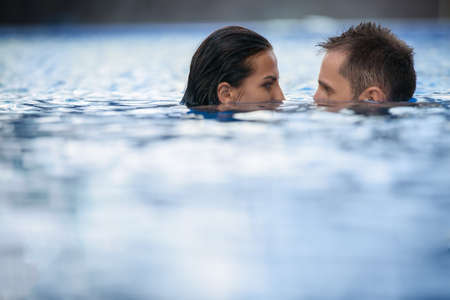 downcast: Unusual tanned young couple indulges in a swimming pool. The dark-haired girl and boy looking at each others eyes downcast face half submerged. Tropics.