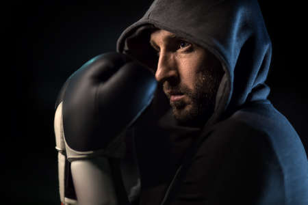 hooded sweatshirt: Confident in a gray hooded sweatshirt in black and white boxing gloves on his hands.It covers their face. Horizontal photo