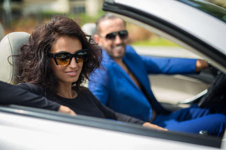 luxuriant: Elegant woman with luxuriant black hair wearing a black dress and a man in a blue suit go in the car. Beautiful girl smiling at the camera. Tropics. Horizontal photo