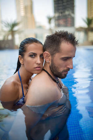 tropics: Young couple basking in the crystal clear outdoor swimming pool. Girl in swimsuit. Tropics. Vertical photo
